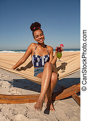 Woman with cocktail glass sitting on hammock at beach in the sunshine