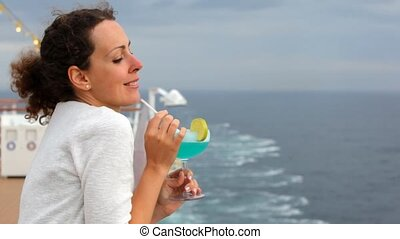 woman with cocktail in hands stands at board by ship and smiles