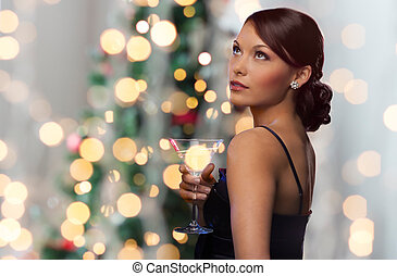 woman with cocktail over christmas tree lights