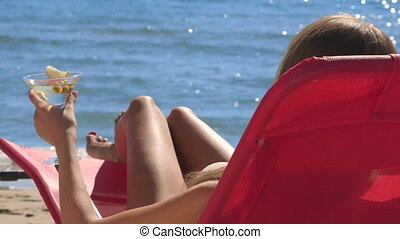 Woman with cocktail relaxing on summer beach resort rear view