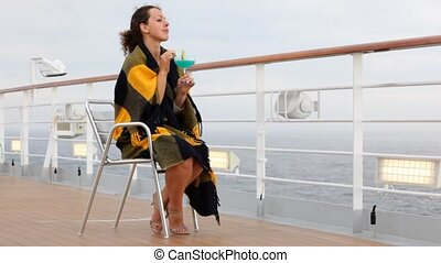 woman with cocktail sits by ship near board and looks afar