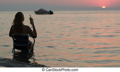Woman with cocktail sitting on chair in sea