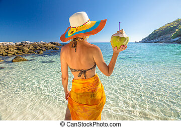 Woman with coconut cocktail - Attractive and tanned woman...
