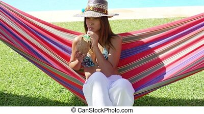 Woman with coconut drink and sitting in hammock