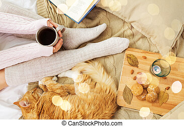 woman with coffee and red cat sleeping in bed