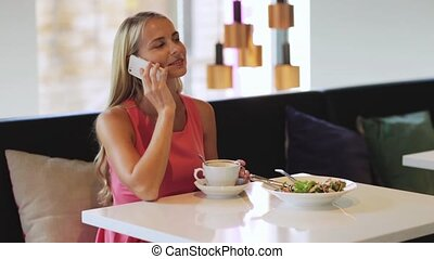 woman with coffee calling smartphone at restaurant