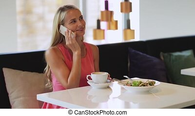 woman with coffee calling smartphone at restaurant -...