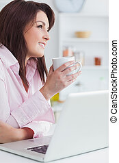 Woman with coffee cup and laptop looking away