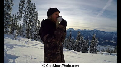 Woman with coffee cup standing on the snow covered landscape 4k