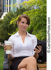 Woman with coffee in the park using smart phone