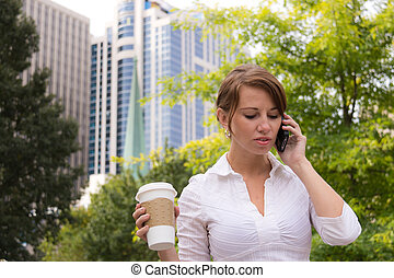Woman with coffee in the urban park using smart phone