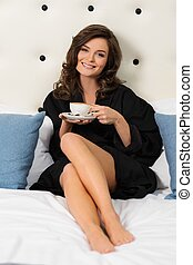 Woman with coffee on a bed in a hotel room