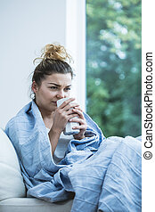 Woman with cold drinking tea