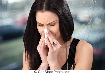 Woman with cold, sneezes and tissue paper in flu season