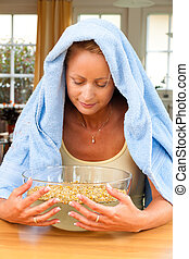 Woman with colds and flu. Inhalation of herbs.