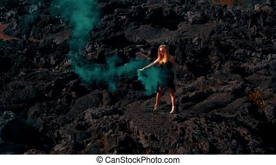 Woman with colored smoke on the volcanic rocky land