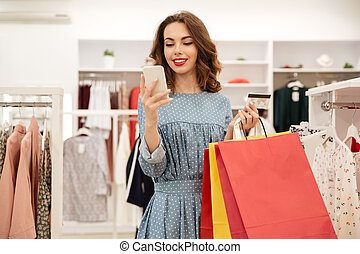 Woman with colorful bags using smartphone