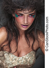 woman with colorful make up looking away from the camera