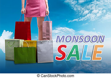 Woman with colorful paper bag on monsoon sale