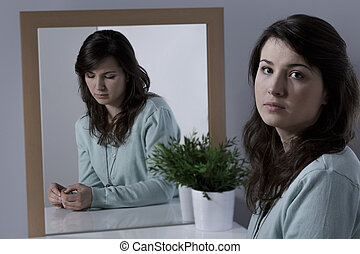 Woman with complexes looking at the mirror