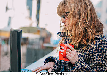 woman with computer and mug on the street outdoors