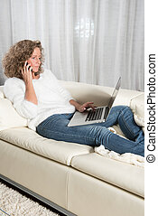 woman with computer on couch having a phone call
