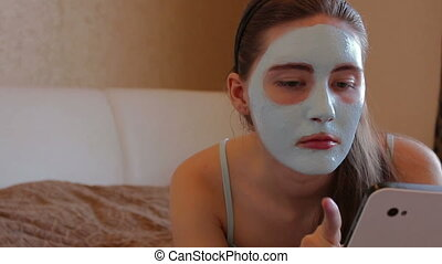 woman with cosmetic mask on her face - girl lying on a bed...