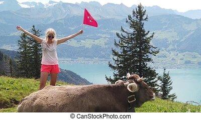 SLOW MOTION: girl with Swiss flag by a cow in alpine meadow along Rigi-Scheidegg railway with spectacular views of Swiss Alps, Schwyz basin, Lake Lucerne. Tourism in Lucerne area, Central Switzerland.