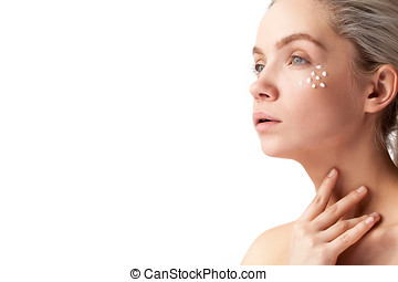 Woman with cream face drops on her face