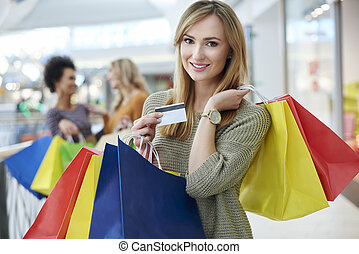 Woman with credit card and full shopping bags