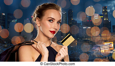 woman with credit card and shopping bags in city