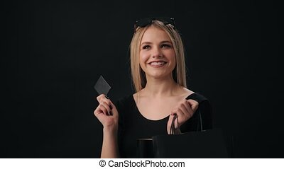 Thoughtful beautiful woman standing in studio with black background and holding credit card and shopping bags. Concept of purchase and shopaholism.