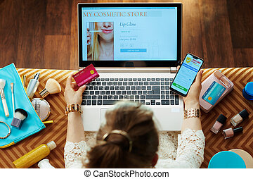 woman with credit card buying cosmetics online on laptop