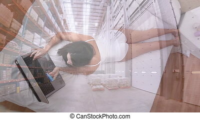 Woman with credit card using laptop against warehouse - ...