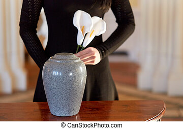 Woman with cremation urn crying in church  Cremation, people and
