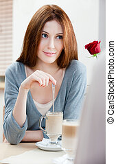 Woman with crimson rose at the cafe