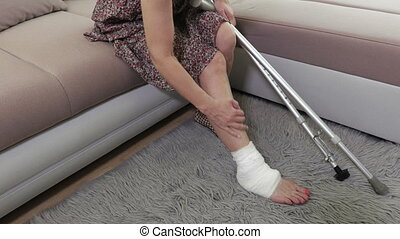 Woman with crutches and injured leg sitting on couch