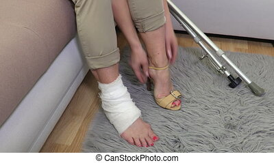 Woman with crutches and leg injury trying high heels