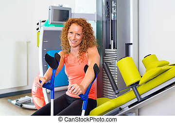Woman with crutches sitting on exercise machine