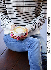 Woman with cup of cappuccino in hands sitting on the wooden floor