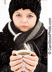 woman with cup of coffee in the winter park