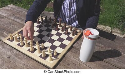 Woman with cup of coffee near chessboard