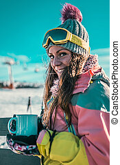 Woman with cup of coffee or tea enjoying the winter day on mountain