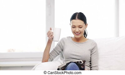 woman with cup of coffee reading magazine at home