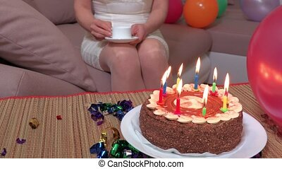 Woman with cup of coffee sitting on sofa near birthday party...