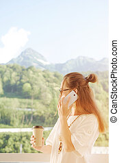 Woman with cup of coffee talking on phone on mountain resort.