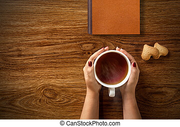woman with cup of tea, cookies and book on wood