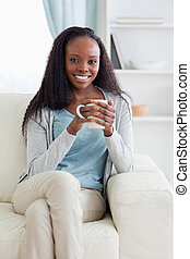Woman with cup on her sofa