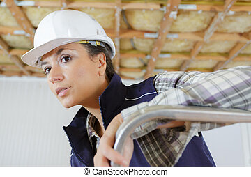 woman with curios expression in builder uniform on ladder ...