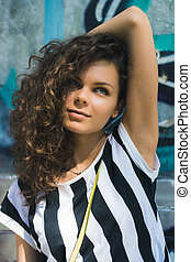 Woman with curly hair in a striped T-shirt standing on a background of graffiti